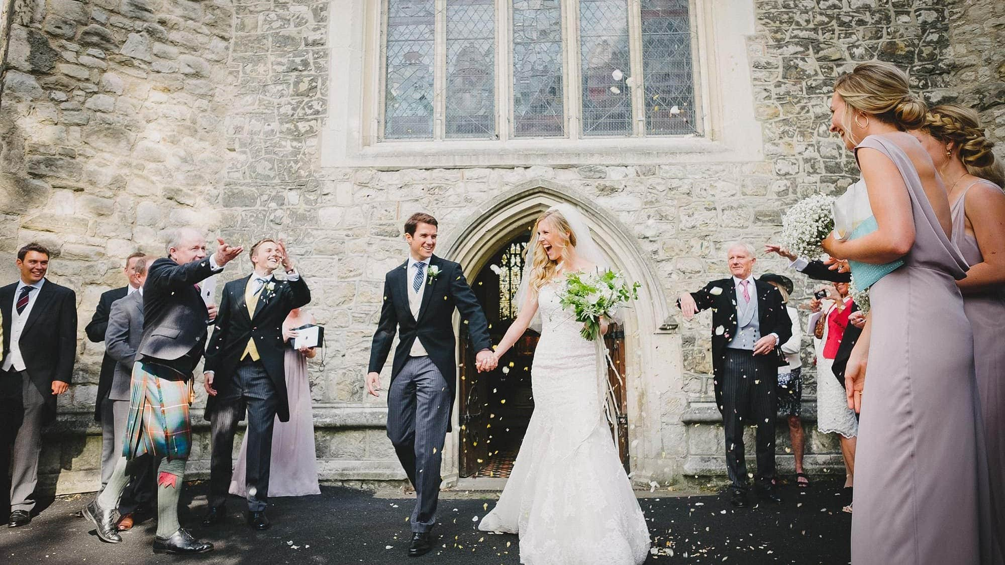 bride and groom's confetti moment outside All Saints Church Fulham