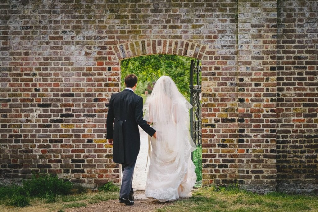 the bride and groom entering the walled garden at Fulham Palace
