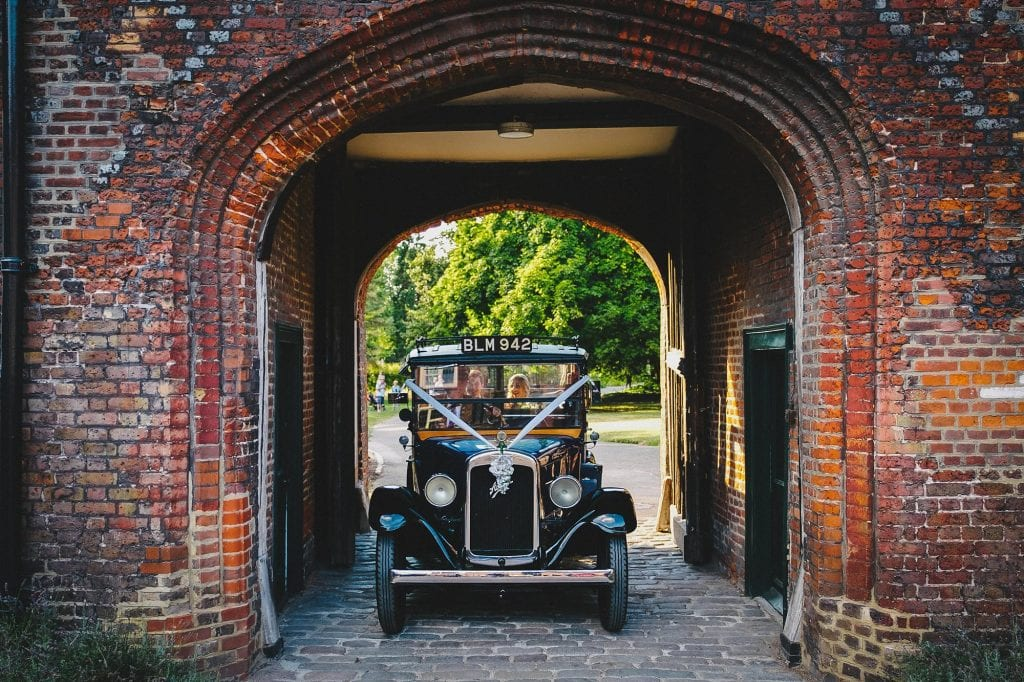 bride and groom make their grand entrance to Fulham Palace courtyard in a classic wedding car