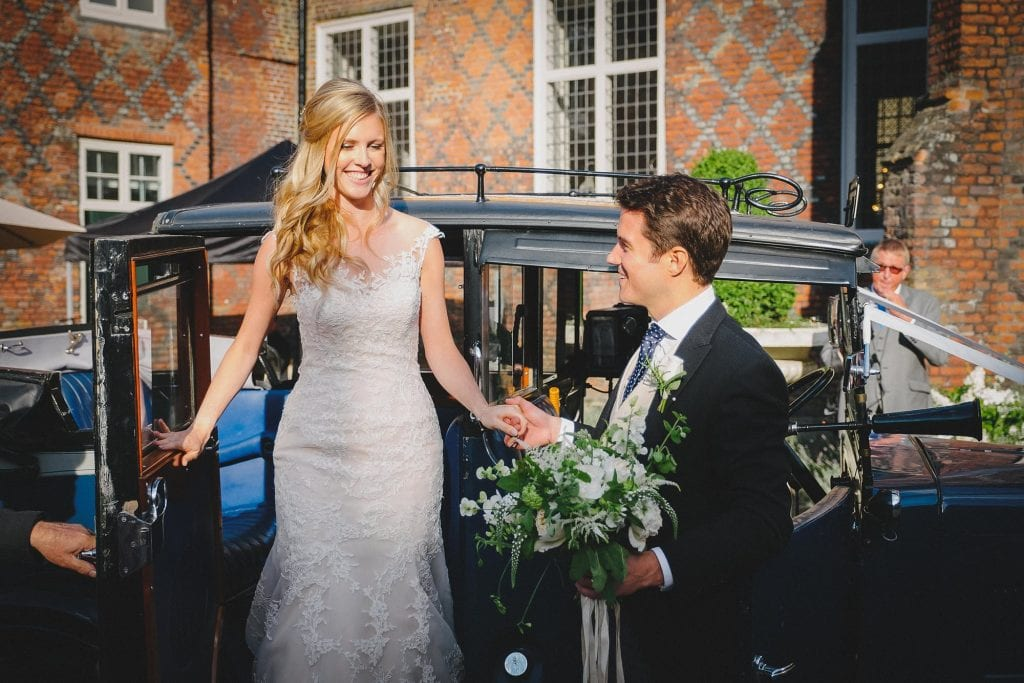 the groom helps his bride out of their classic wedding car