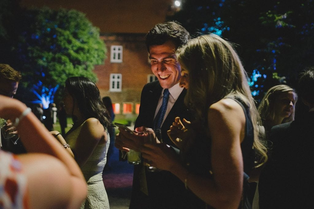 guests laughing at something on a phone during a wedding reception