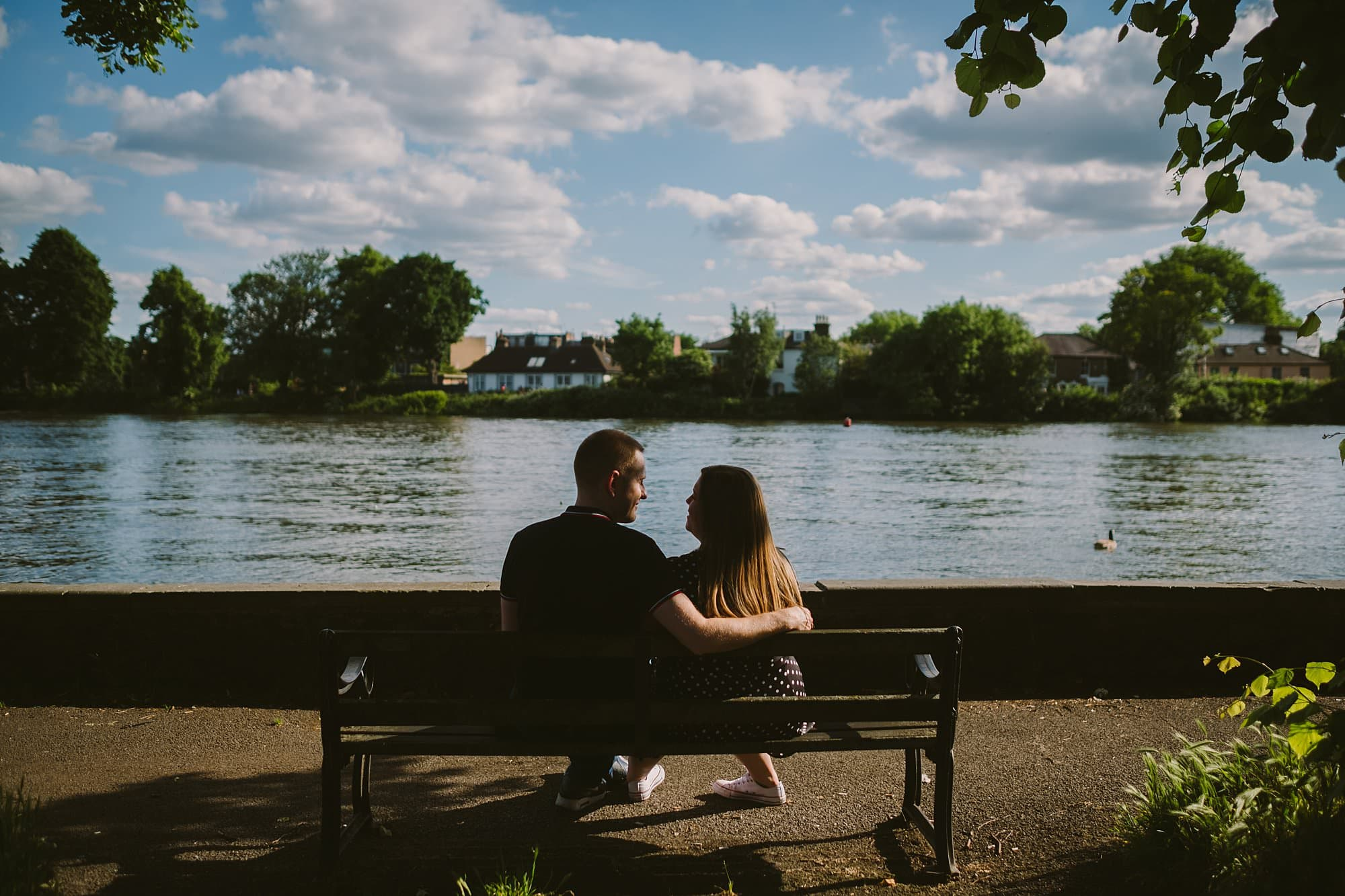 engaged couple sitting on a bench by the thames