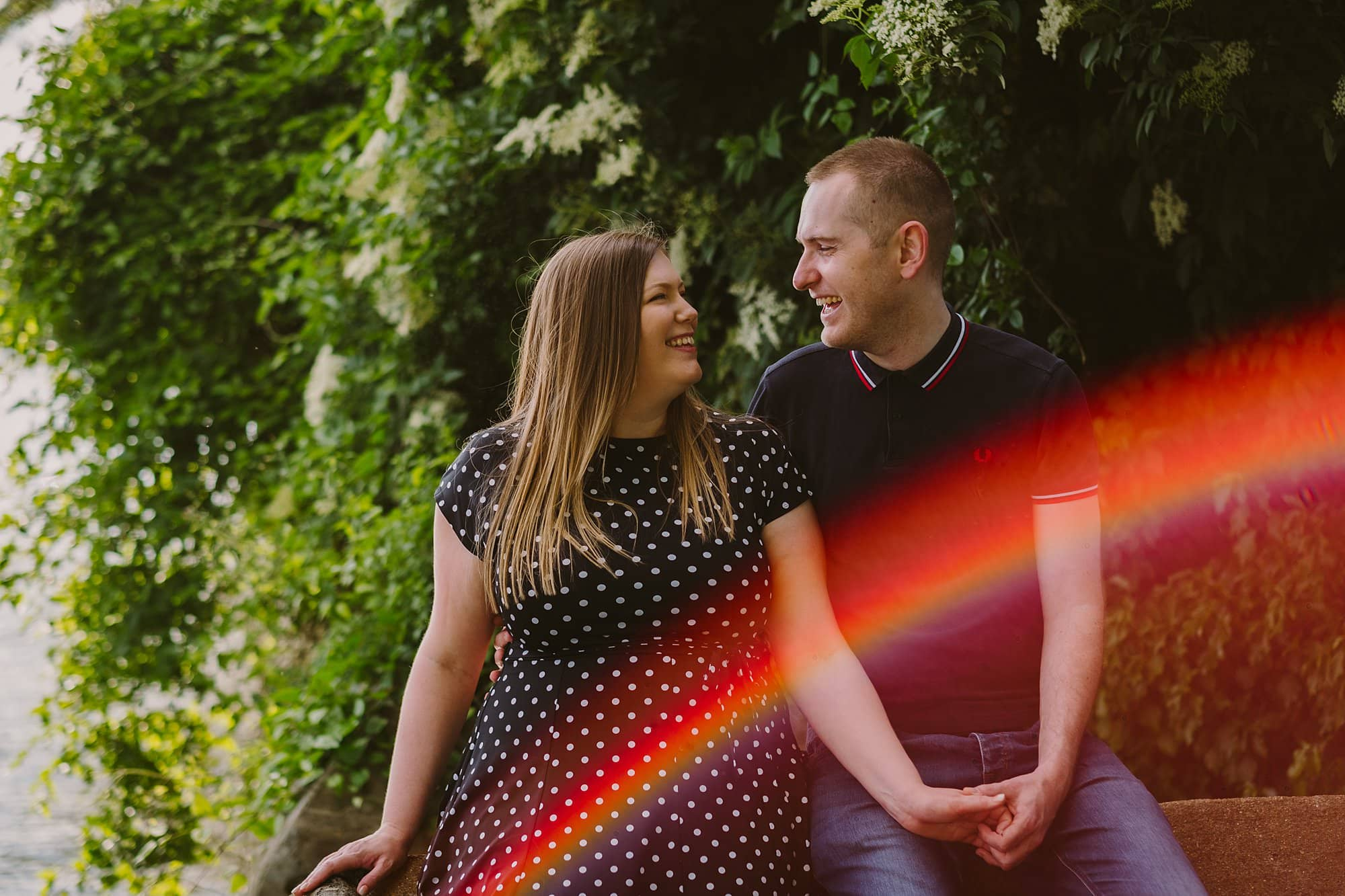 couple sitting together with a rainbow lens flare
