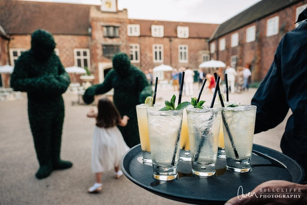 a little girl plays with the Hedge People in the courtyard at a Fulham Palace wedding