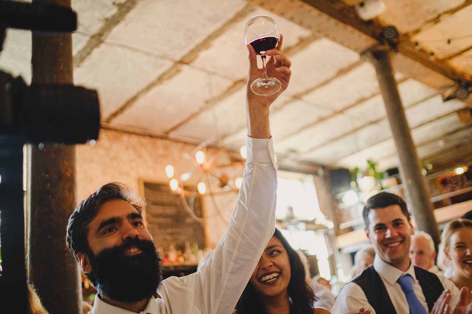 main with beard raising a glass of red wine during wedding speeches