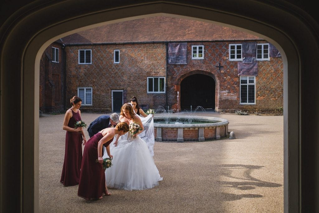 bridesmaids attend to the bride's wedding dress just before her wedding ceremony