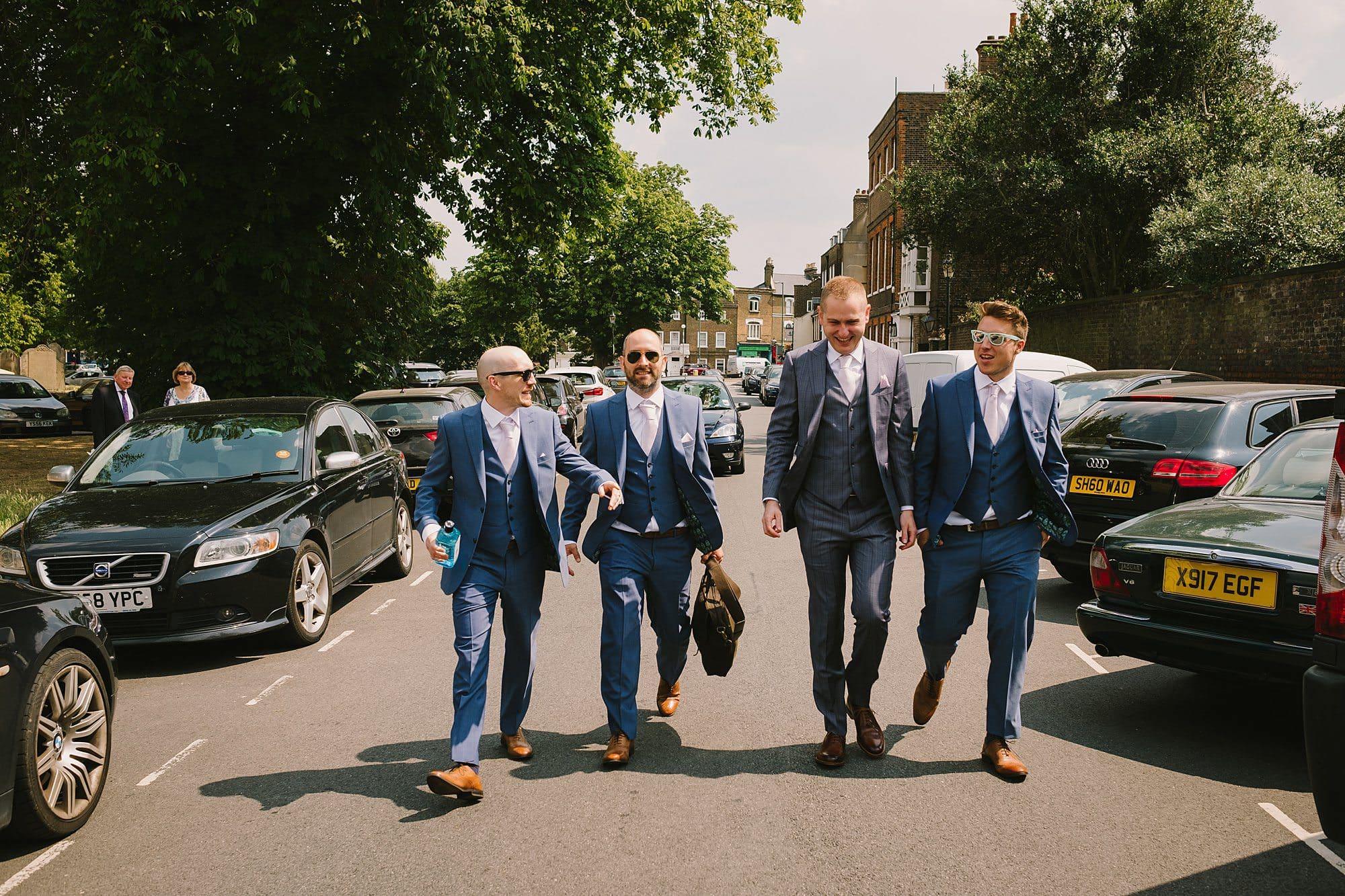 groom and his friends walk towards a kew gardens wedding