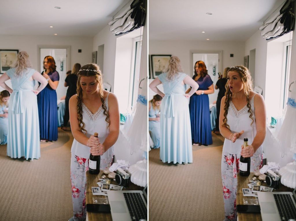 bride popping the champagne at bridal prep before a lechlade wedding in the cotswalds