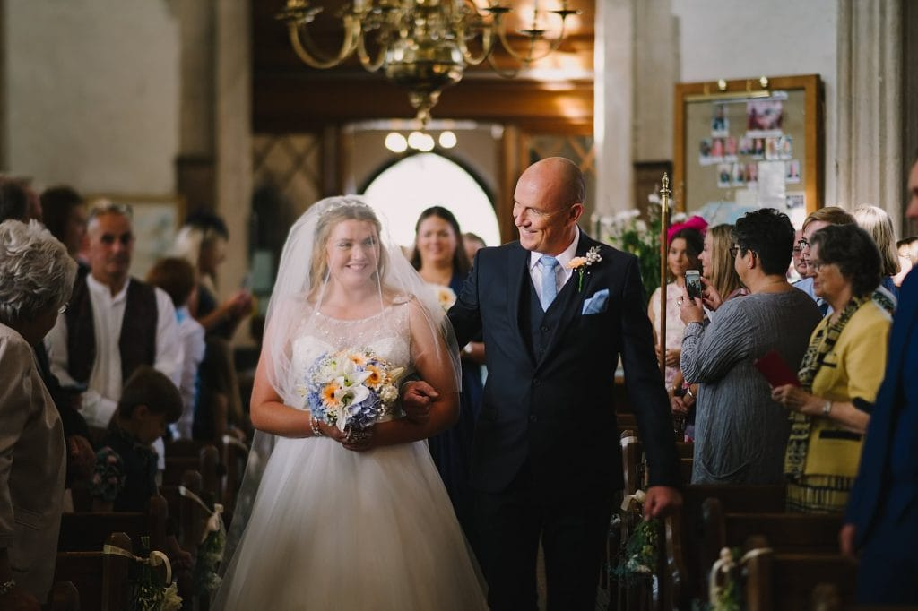 bride and her father walking down the aisle at st lawrence church lechlade