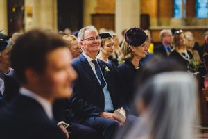 father of the groom steals a glance at the happy couple in the church