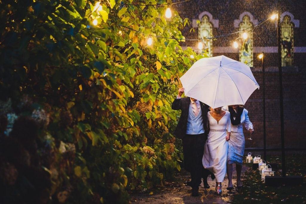 the bride and groom run to their wedding breakfast under an umbrella