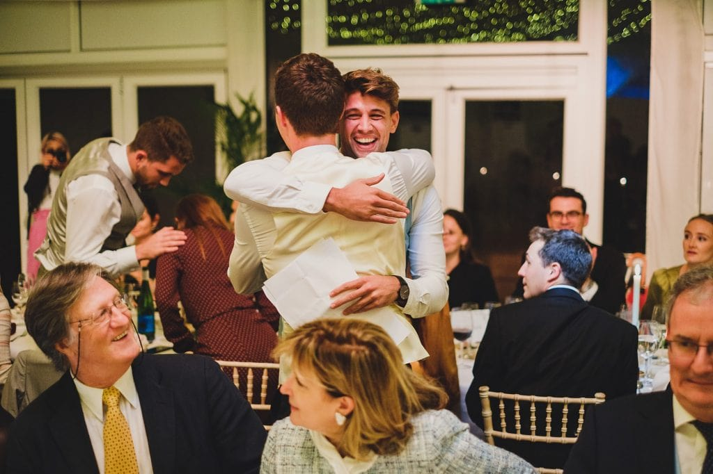 groom and best man hugging after the wedding speeches