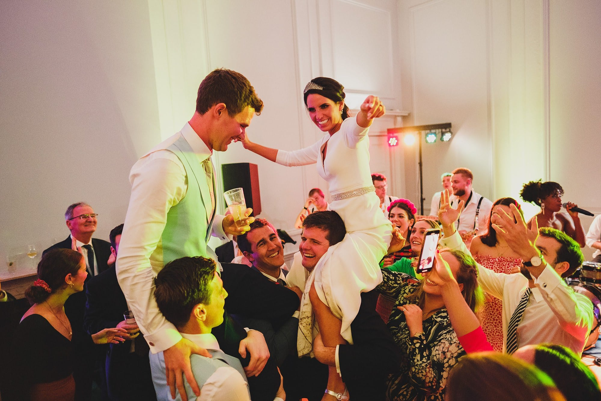 bride and groom carried onto the dancefloor on their guests shoulders