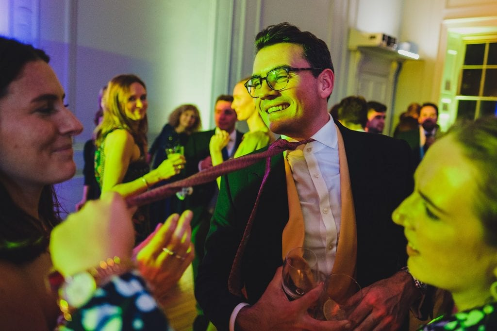 a wedding guest is dragged by his tie onto the dance floor