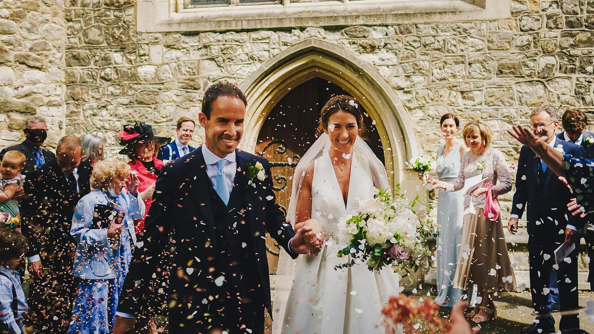 bride and groom and confetti at all saints church Fulham