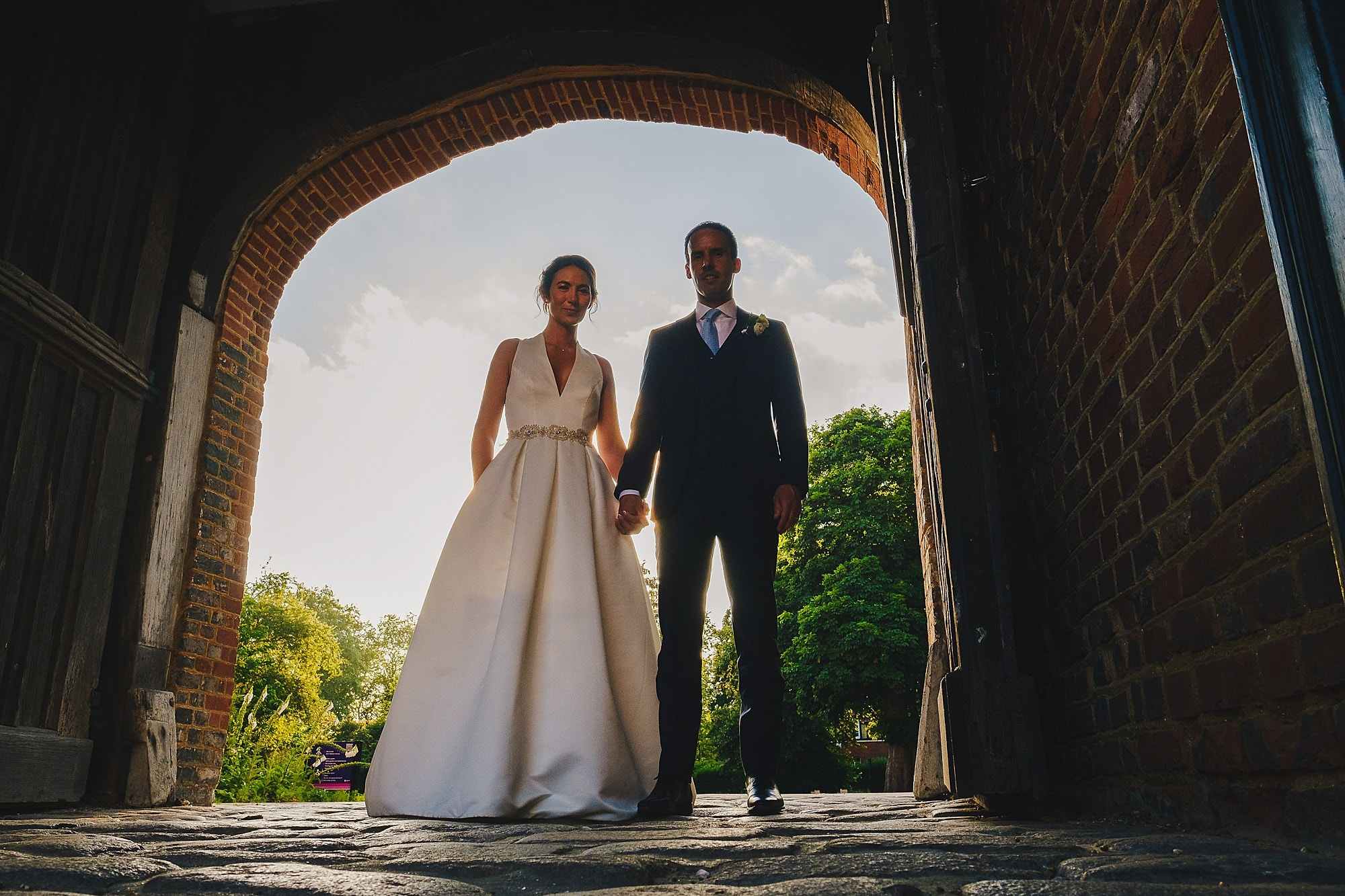 bride and groom portrait in main entrance to Fulham Palace courtyard